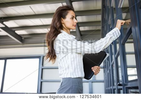 Businesswoman knocking on door in office