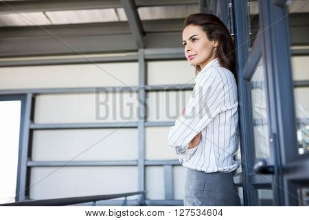 Beautiful businesswoman young leaning on office door