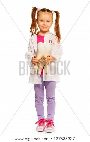 Whole-length portrait of cute little girl wearing whites playing dentist, isolated on white background