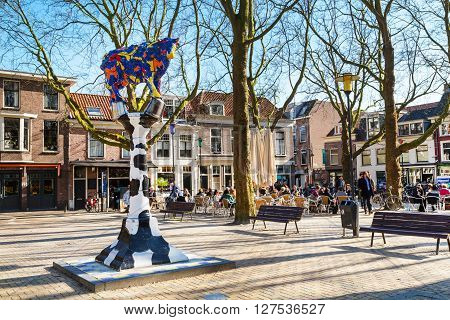Delft, Netherlands - April 8, 2016: Colorful cow sculpture, cafe, traditional dutch houses on the square, bicycles, people in downtown of popular Holland destination Delft