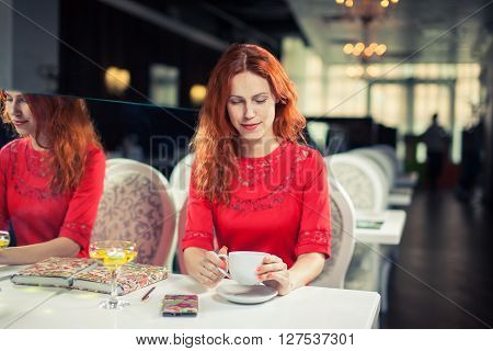 Beautiful  woman using  laptop, phone at table in cafe