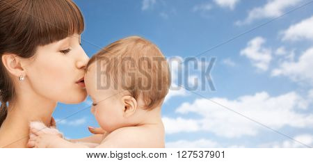 family, children and people concept - happy mother kissing baby boy over blue sky and clouds background