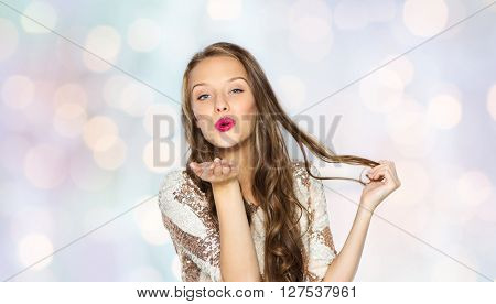 people, style, holidays, hairstyle and fashion concept - happy young woman or teen girl in fancy dress with sequins and long wavy hair sending blow kiss over holidays lights background