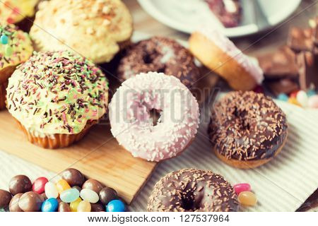 sweet food, junk-food and eating concept - close up of glazed donuts, candies and muffins on wooden board