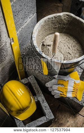 Tools for bricklayer bucket with a solution and a trowel close-up