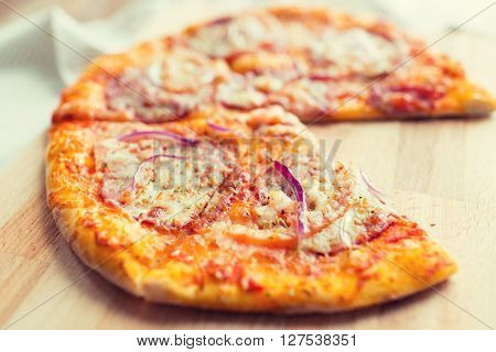 fast food, italian kitchen and eating concept - close up of homemade pizza on wooden table