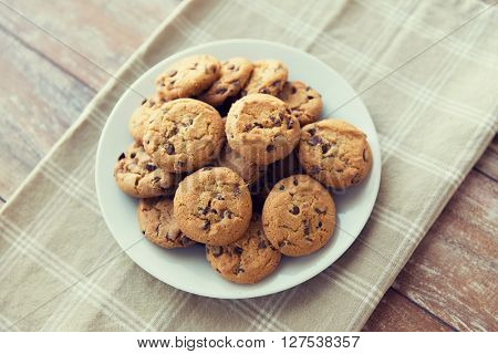 food, junk-food, culinary, baking and eating concept - close up of chocolate oatmeal cookies on plate
