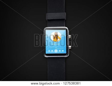 modern technology, object and media concept - close up of black smart watch with music player application