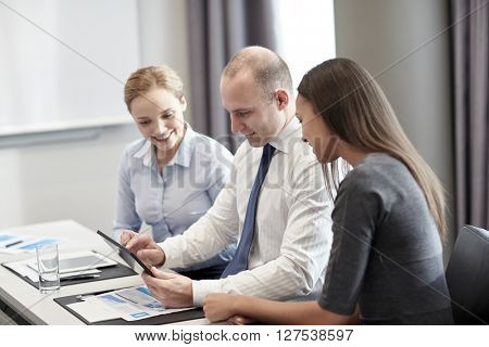 business, people and technology concept - smiling business team with tablet pc computer meeting in office