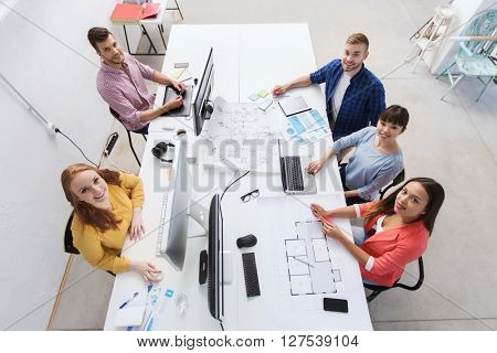business, startup and people concept - creative team with computers, blueprint and scheme at office