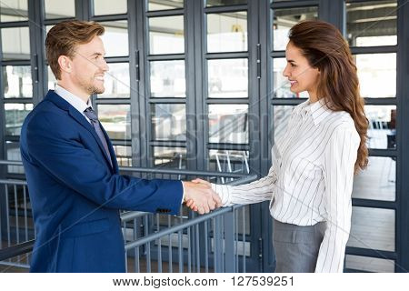 Businessman shaking hands with businesswoman in office
