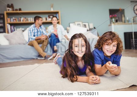 Portrait of happy children lying on carpet while parents in background at home