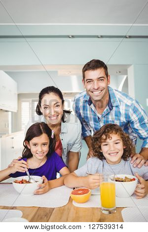 Portrait of cheerful man and woman with children having breakfast at home