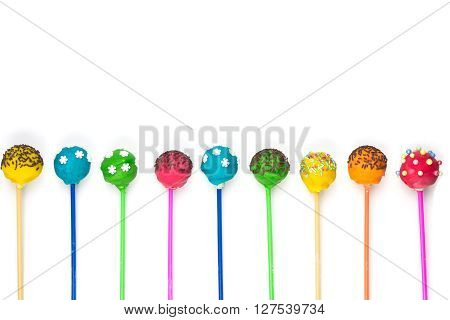 Row of colored cakepops on isolated background