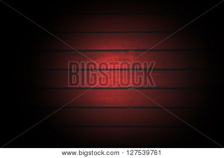 Old dark red painted wooden wall with light spot in the center - texture or background