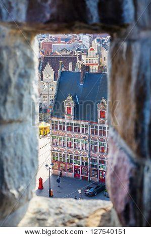 Ghent, Belgium - April 12, 2016: Aerial view of Ghent, Belgium square and medieval buildings through window