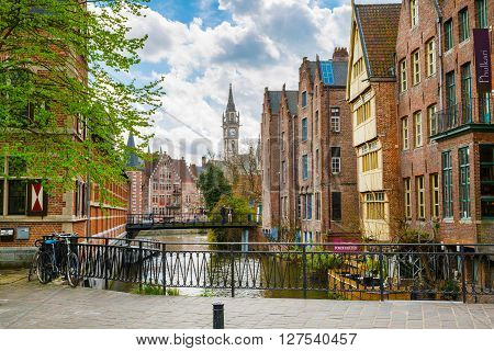 Ghent, Belgium - April 12, 2016: Downtown of Ghent with canal, clock tower, medieval buildings, Belgium