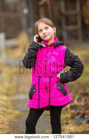 Little girl standing on the street talking on a cell phone.
