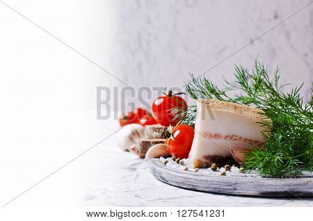 Salty lard with spices on a background of vegetables. Selective focus.