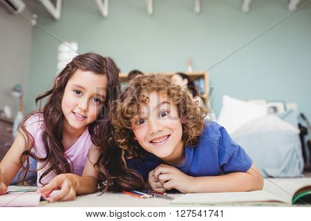 Close-up portrait of children smiling while studying at home