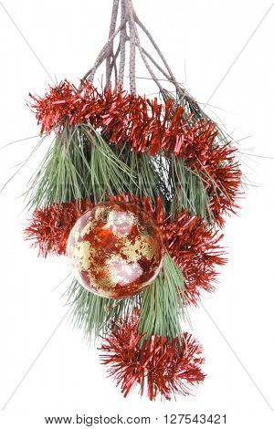 metallic christmas holiday toys with shiny red garland on fir tree twig isolated over white background