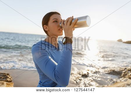 Woman drinking water on beach