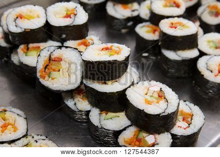 Many beautifully decorated sushi on a plate