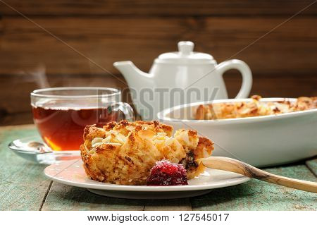 Panettone pudding and steaming hot black tea on shabby wooden background horizontal