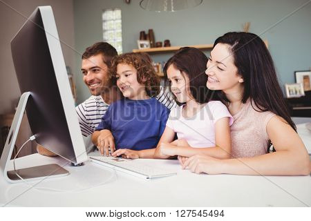 Close-up of happy family looking in computer at home