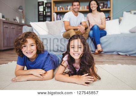 Portrait of happy siblings lying on carpet against parents siting on sofa