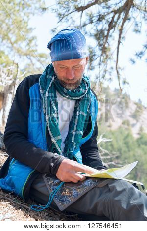 Bearded man hiker wearing a scarf sitting with map ponders route. Sunny day in forest.