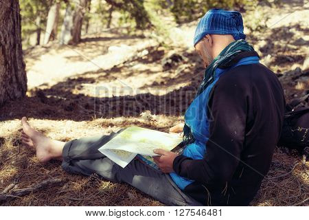 Bearded man hiker wearing a scarf sitting with map ponders route.