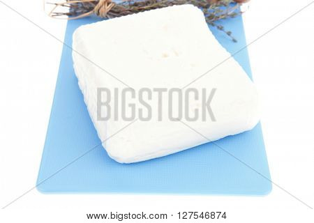 white goat cheese on cutting plate with tomato thyme and garlic isolated over white background