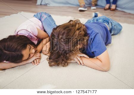 Close-up of siblings relaxing on carpet at home