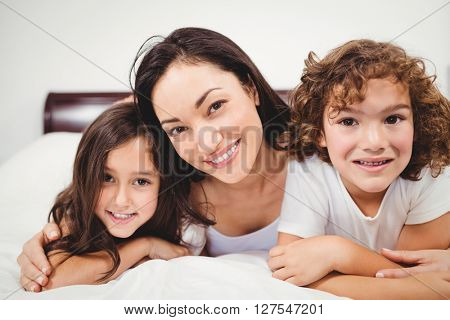 Close-up portrait of cheerful woman with children lying on bed at home