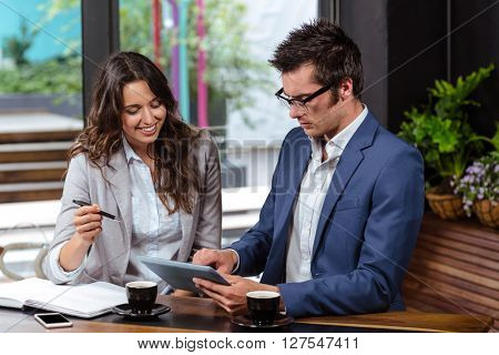People using tablet and notebook in a cafe