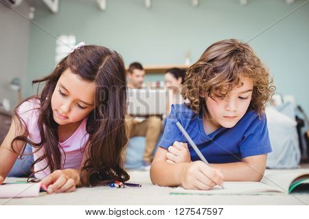 Close-up of children studying while parents in background at home