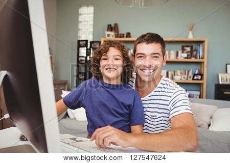 Close-up portrait of cheerful father and son using computer at home