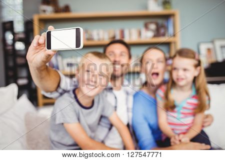 Man taking selfie of family with mobile phone while sitting on sofa at home