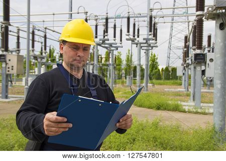 Technician with yellow helmet inspect high voltage power station
