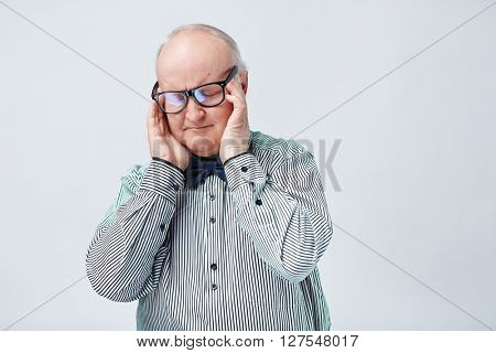 Elegant senior man in eyeglasses and striped shirt touching his temples