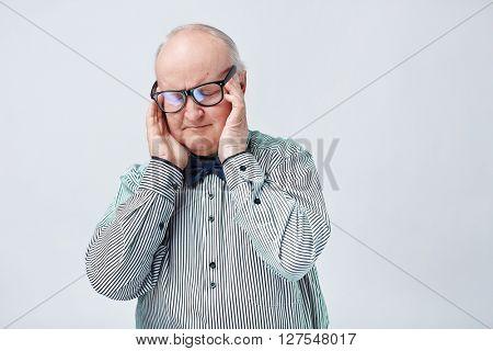Elegant senior man in eyeglasses and striped shirt touching his temples