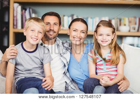 Portrait of cheerful family sitting with sofa against shelf at home
