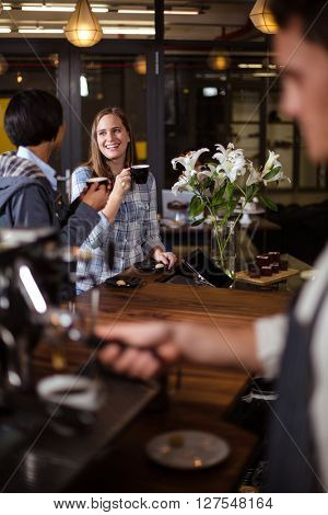 Smiling women having coffee in a bar