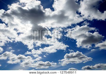 gray clouds with solar illumination in the blue sky