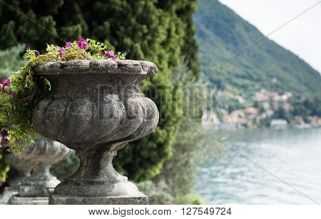 closeup of a stone flower vase with Lake Como (Italy) in the background
