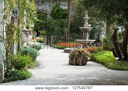 Varenna, Italy - September 4th 2015: woman walking through the botanical garden at Villa Monastero in Varenna Italy.