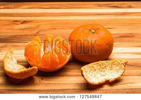 A whole tangerine and a half peeled tangerine on a teak cutting board