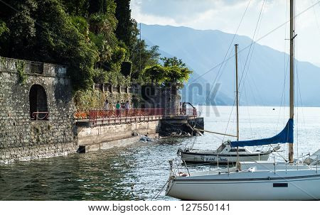 Varenna, Italy - September 4th 2015: tourists walking on the lakeside promenade in Varenna (Lake Como Italy) with two white boats in the foreground.