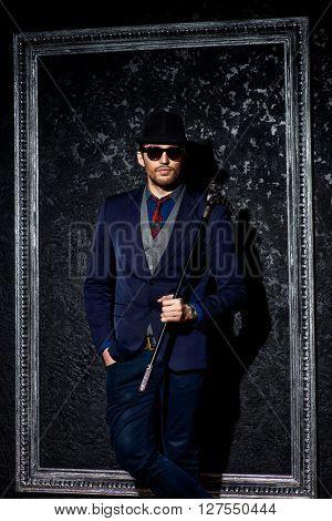 Portrait of a fashionable male model wearing elegant suit. Studio shot.